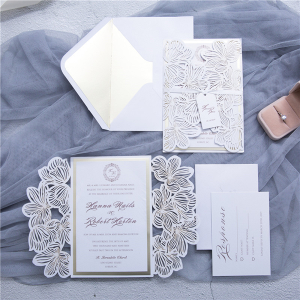 white floral gate card invitation suite with white ribbon tag