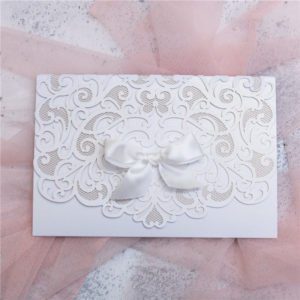 white folded card invitation suite with white bow